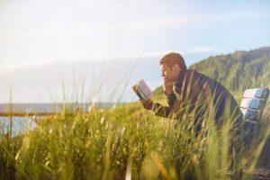 Man by lake reading a book