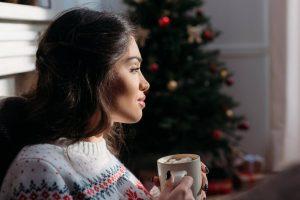 Woman enjoy hot chocolate by Christmas Tree