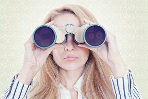 Blonde woman in blue and white stripe shirt looking through binoculars