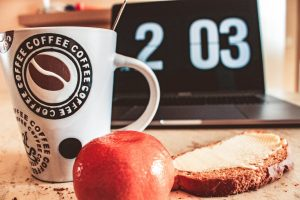 Table with coffee mug, apple, bread and digital clock