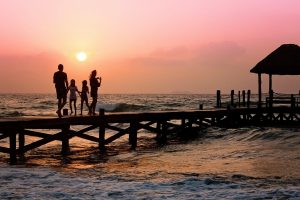 Family with two children walking on pier at beach
