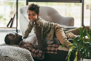 African American man playing with his son on couch