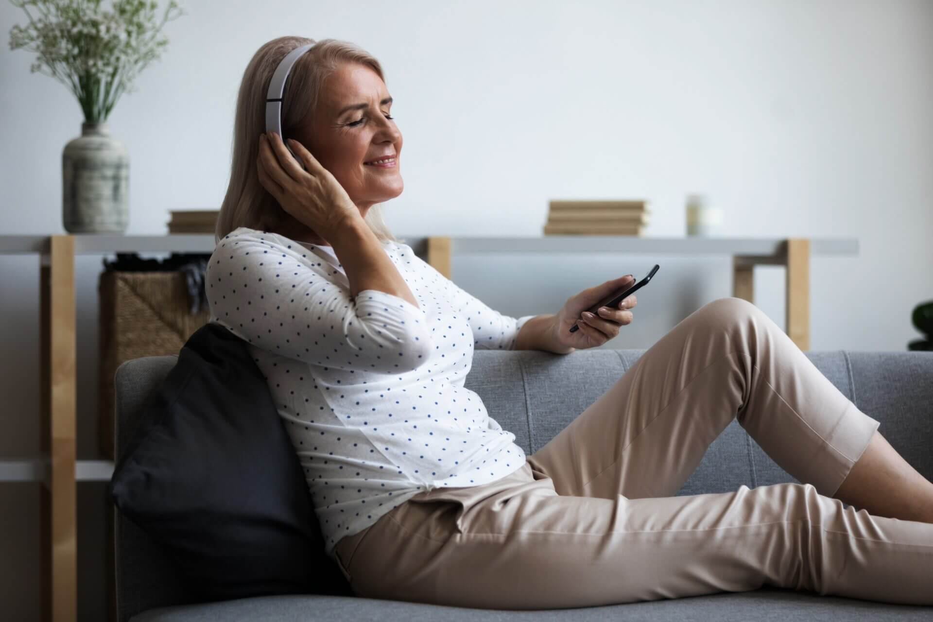 Woman relaxing on couch listening to calming apps